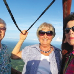 """FiftyForward Madison Station members Shirley Manaley (left), Mille Harris (center), Shirley Kerkvliet (right), Don Wilkerson (not pictured) and FiftyForward Afternoon Office Manager Julie Reeves (not pictured) took to the skies to fulfill a long-anticipated FiftyForward First. The hot air balloon ride was a dream come true for several members. Shirley Kerkvliet said of the experience, """"It was money well spent. At first, I thought I would be scared, but we moved so slowly ... it was beautiful. Riding in a hot air balloon was certainly a brand new experience for me but something I had always wanted to try. It was a thrill."""""""