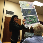 Councilwoman Mina Johnson presenting early project blueprints at a community meeting in April.