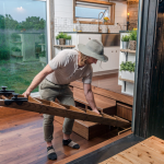 David Latimer, of New Frontier Tiny Homes, slides into place a custom 8 person dining table in one of his company's tiny homes.