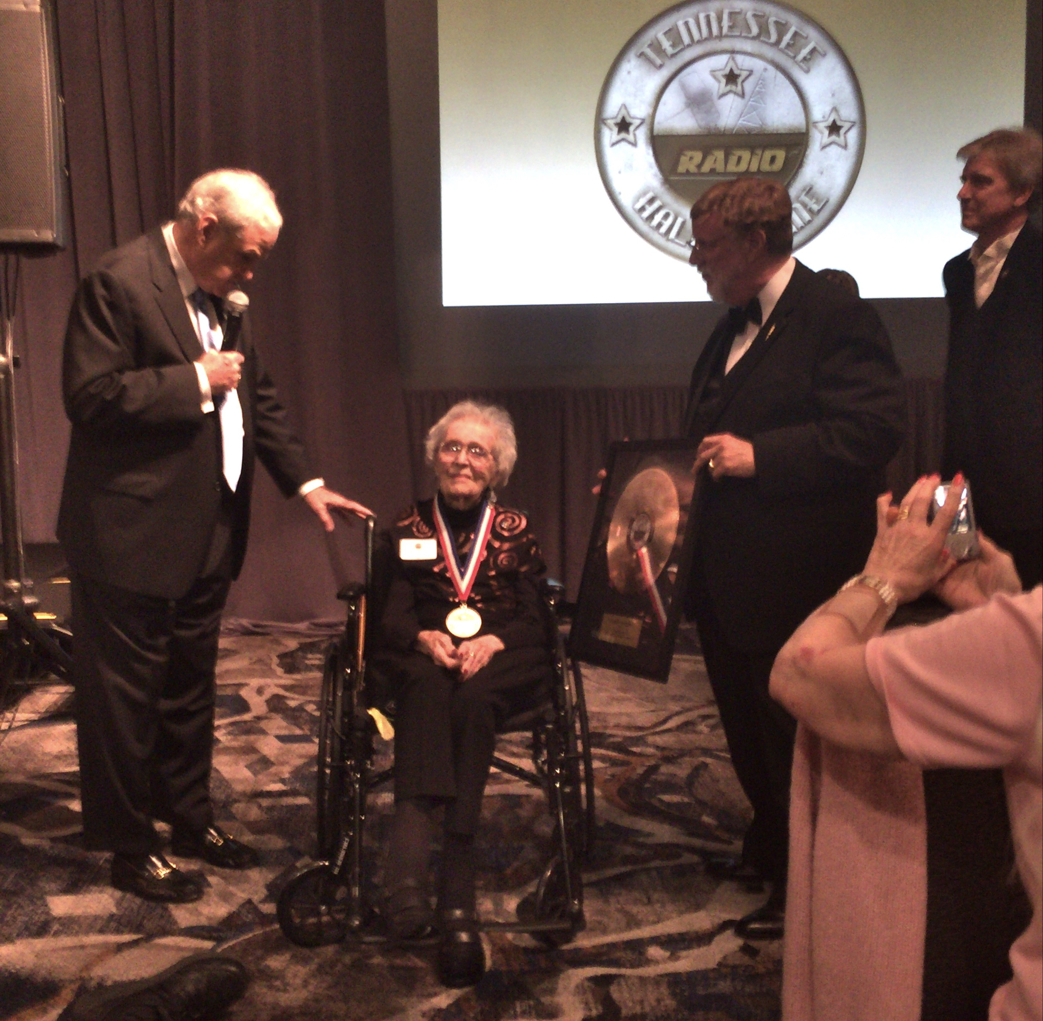 (l-r) Master of Ceremonies John Young with TNRHoF inductee Lin Folk and directors Paul Tinkle and Chip Chapman.